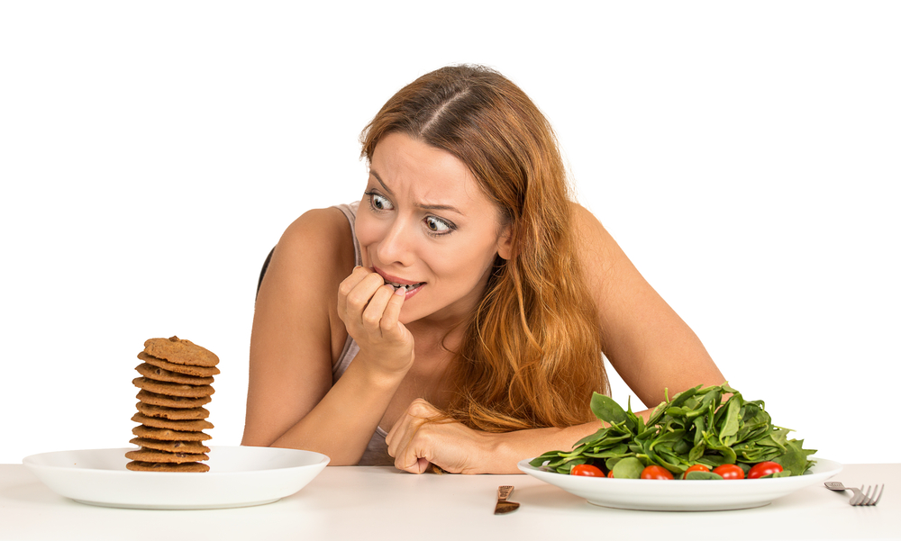 Portrait young woman deciding whether to eat healthy food or sweet cookies she is craving sitting at table isolated white background. Human face expression emotion reaction. Diet nutrition concept-1