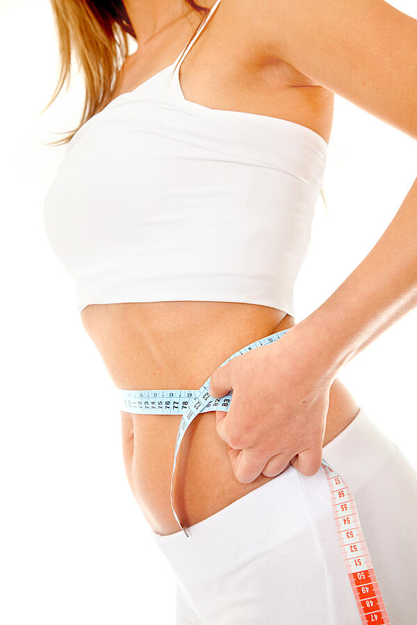 Woman measuring her waist isolated over white